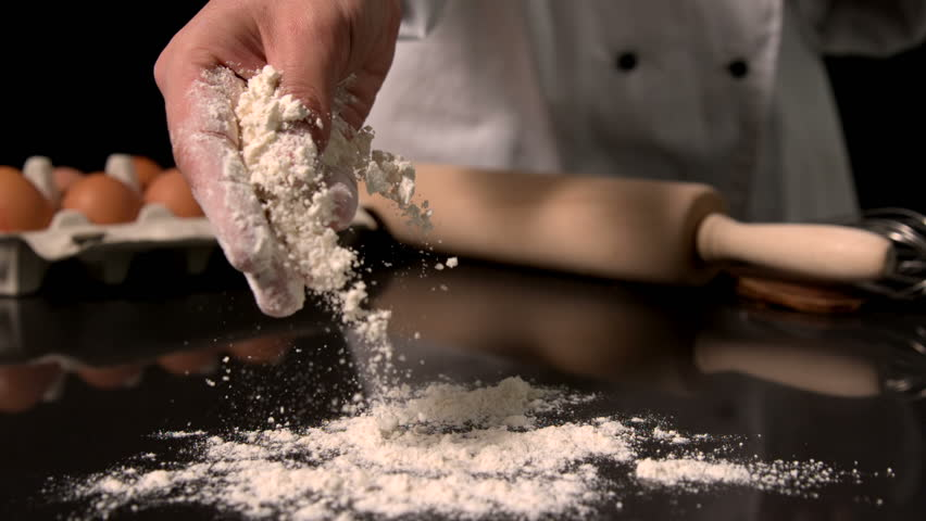 Chef sprinkling flour on black surface in slow motion