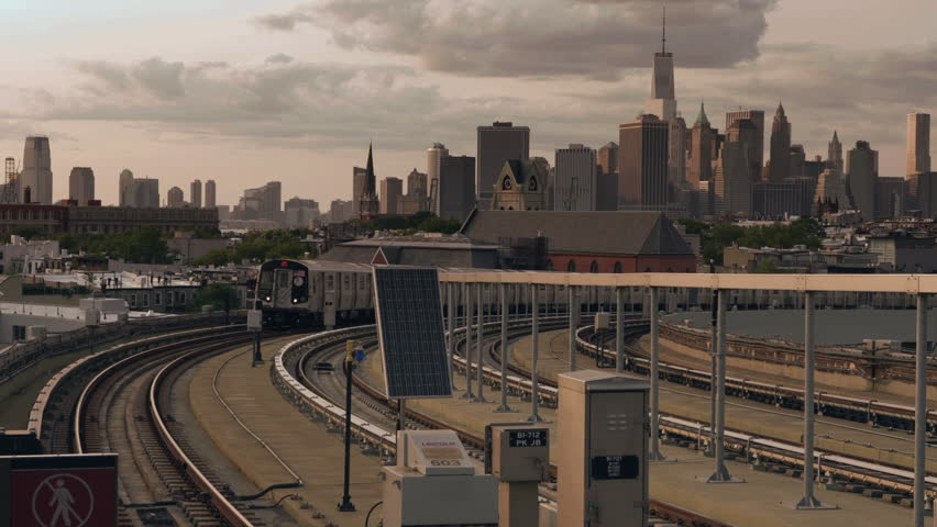 NEW YORK - AUGUST 8, 2014: Manhattan Skyline and F train on elevated MTA subway tracks at sunset in 4K in New York. NYC subway is a rapid transit system leased to the NYC transit authority in USA.