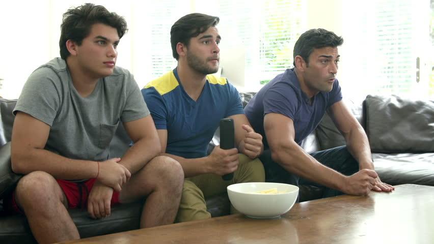 Three Men Sitting On Sofa Watching TV Together