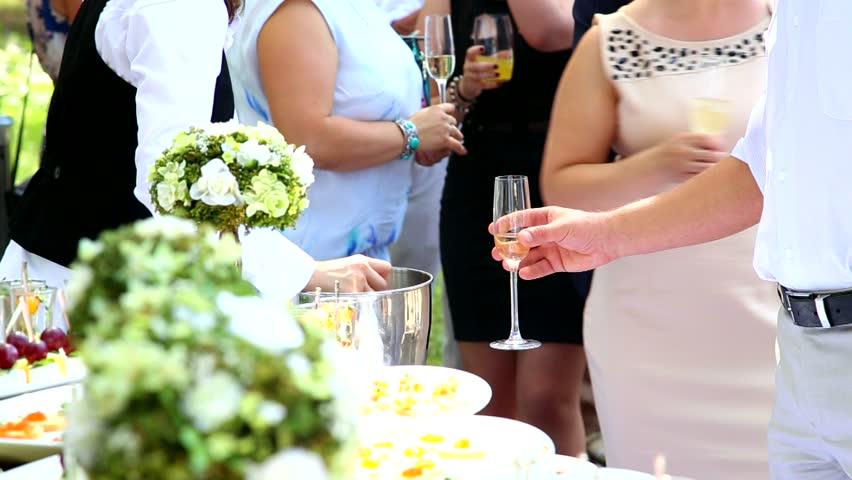 waiter is putting ice in glasses with juice and champagne. catering - HD stock footage clip