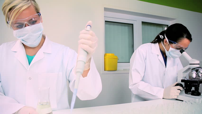 Two medical researchers working with microscopes & test tubes in laboratory conditions - HD stock footage clip
