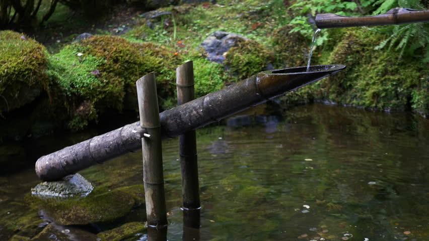 Bamboo tube and flowing water in japanese garden shishi for Bamboo water garden