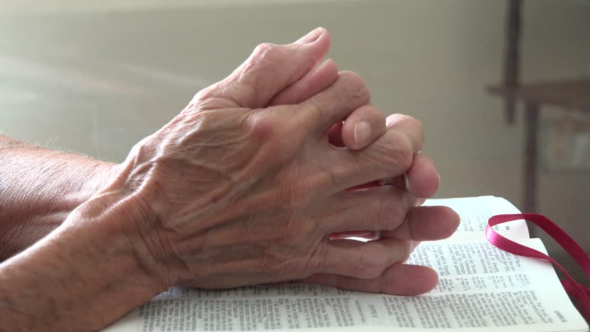 Senior elder woman praying with hands clasped over the Bible. Elderly woman in her daily Christian devotional at home