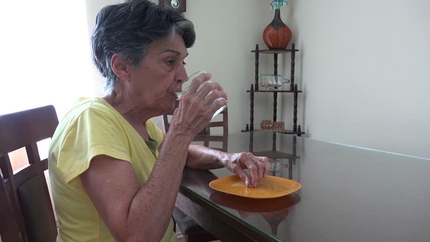 Senior citizen drinking her daily pills and vitamins. Elder woman taking her medications.