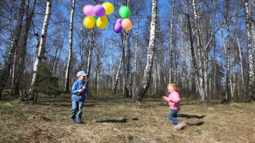 boy holds bunch of balloons and little girl runs around in spring forest  - HD stock video clip