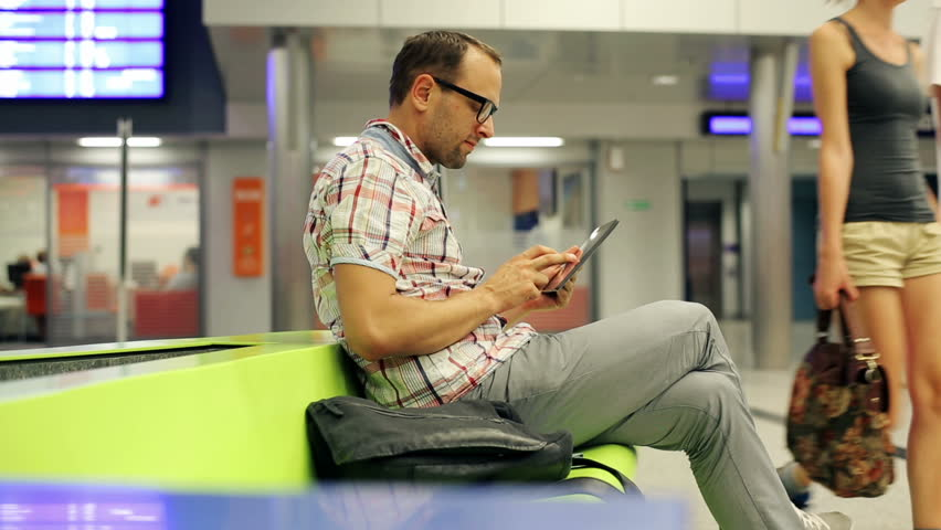 young man with tablet sitting in the train station