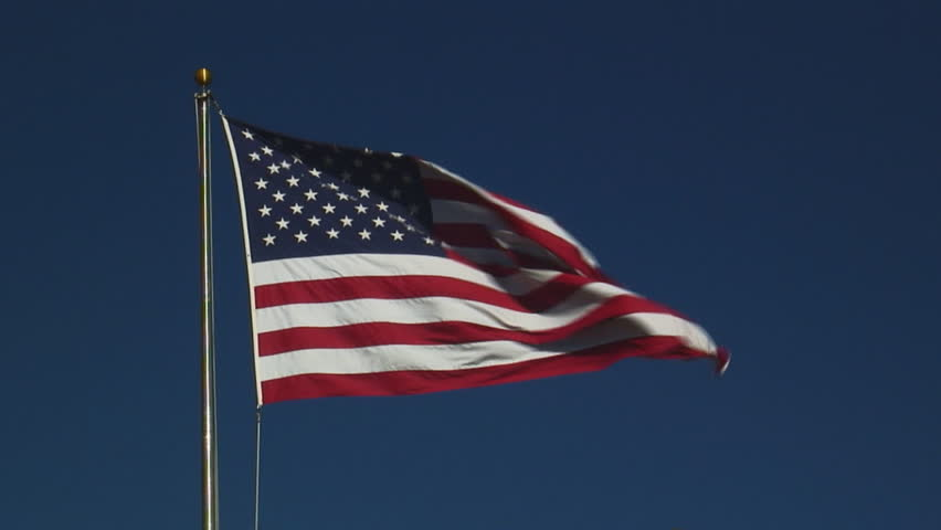 real United States of America flag flying on flagpole against clear blue sky - HD, no audio, medium shot - HD stock video clip