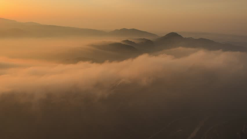 Golden, rose colored clouds after sunrise at Montserrat, Catalonia, Spain. Timelapse footage.