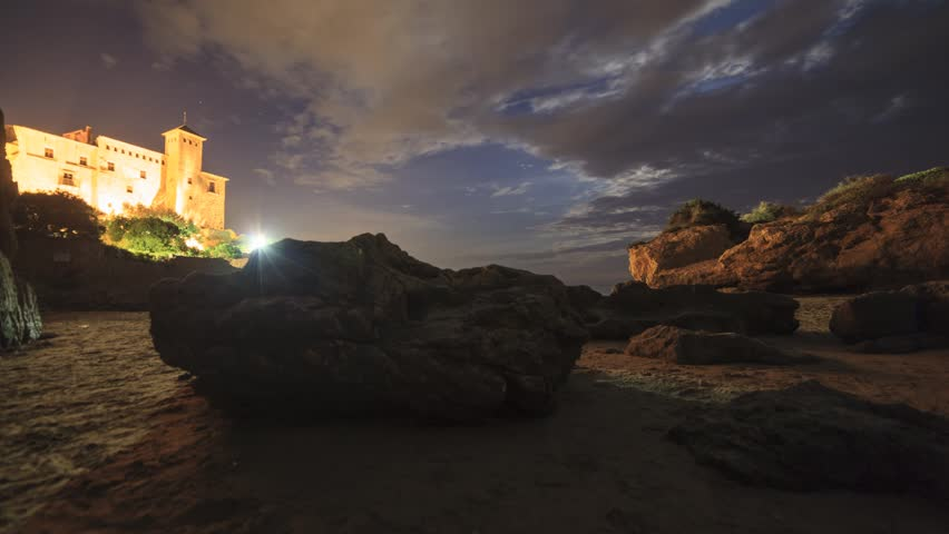 Moonrise at Tamarit Castle over the Mediterranean Sea, in Catalonia, Spain.  Timelapse with dolly movement.