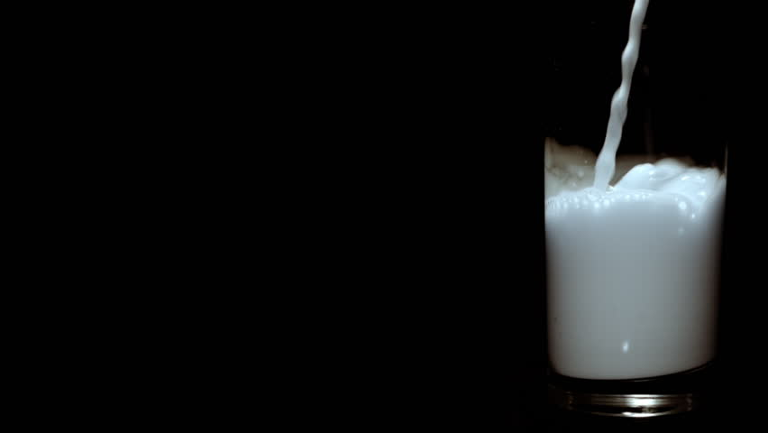 Slow motion clip of milk being poured in glass on black background. (165 fps / HD-Highspeed-Camera)