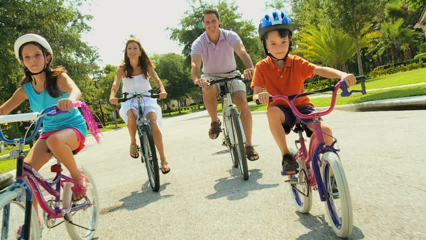 Attractive healthy caucasian family enjoying keeping fit together cycling outdoors 60FPS