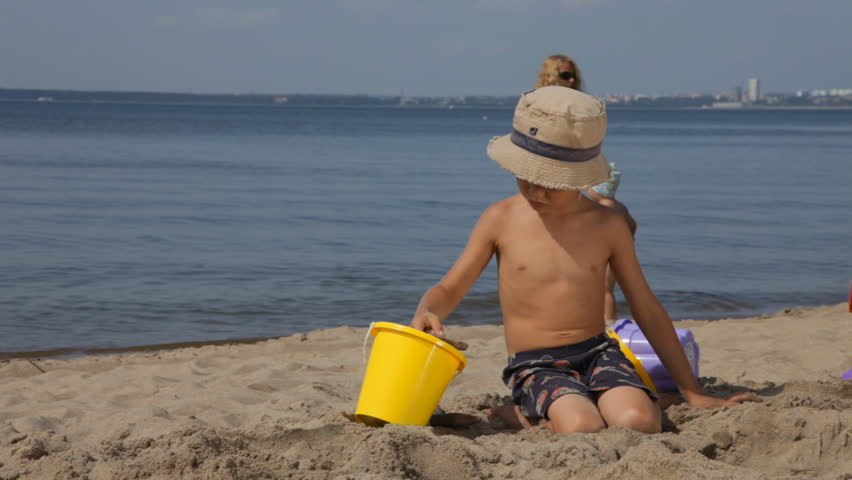 Boy in hat playing with sand on the beach. Mother with little child are on the background. - HD stock video clip