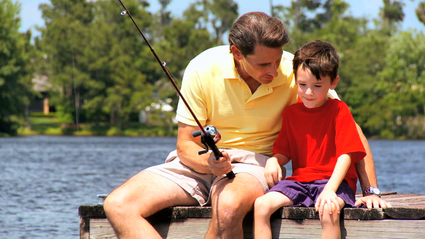 Father encouraging confidence in his young son while learning new sporting skills - HD stock video clip