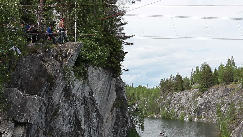 RUSKEALA, KARELIA, RUSSIA - CiRCA JUNE, 2012: Man is ready to jump with bungee rope from rock. The Ruskeala Park with green marble indundated quarry is touristic famous place in Karelia - HD stock footage clip