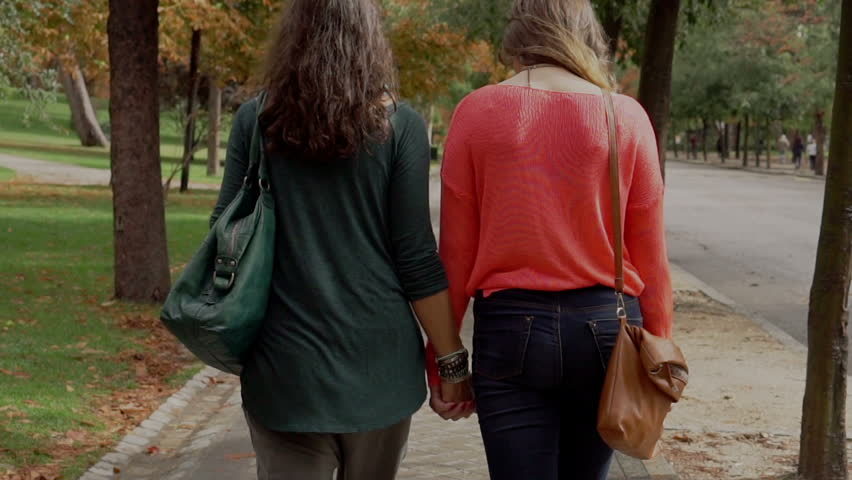 Homosexual Couple Walking In The Park And Holding Hands