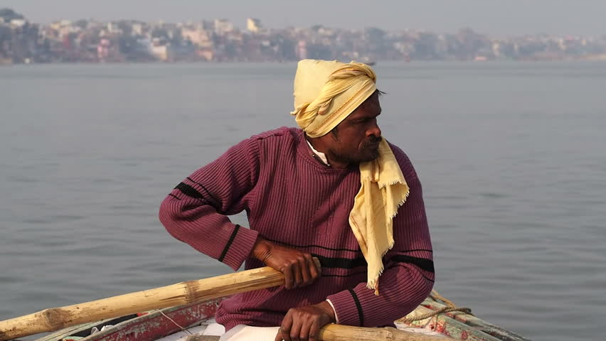 VARANASI, INDIA - FEBRUARY 20, 2013: Unidentified boatman of Indian ethnicity paddling on the sacred Ganges river in Varanasi, Uttar Pradesh, India.
