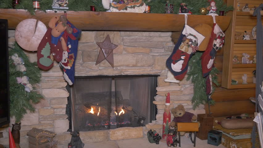 Traditional christmas mantle over burning fireplace with for Stocking clips for fireplace