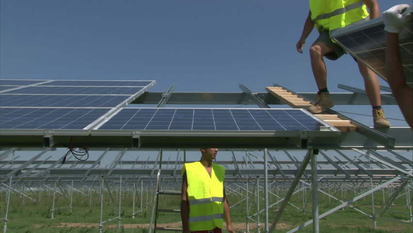 Workers are mounting panels on solar powerplant construction.  - HD stock video clip