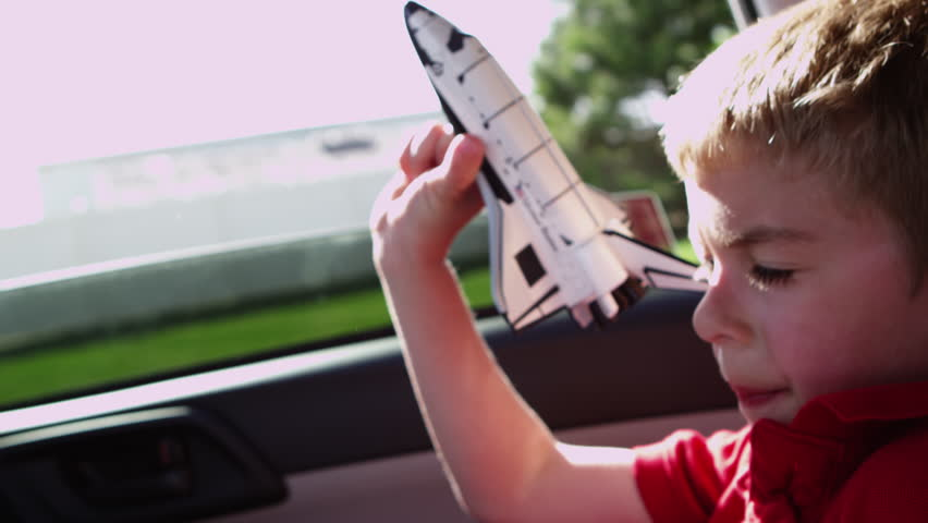 Closeup of boy playing with toy shuttle