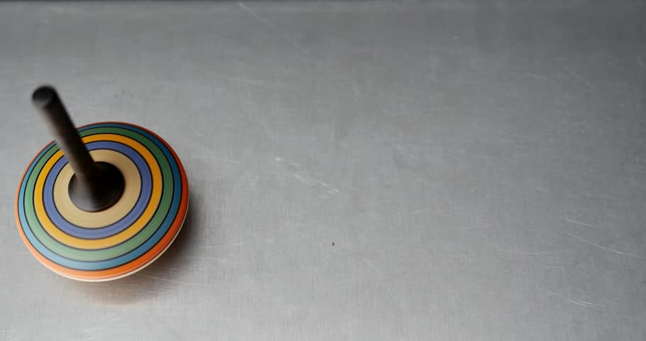 High shot of a colorful spinning top spinning on a metal table/Who´s gonna spin longer - 4K stock footage clip