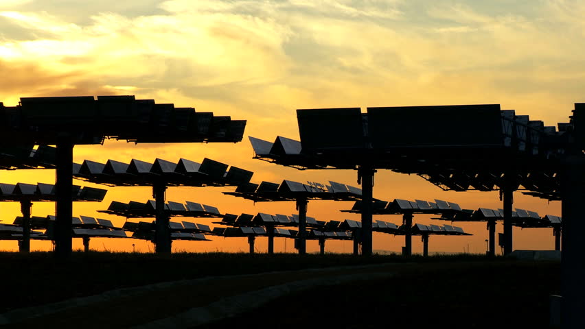 Photovoltaic solar energy panels in silhouette from early morning sun - HD stock footage clip