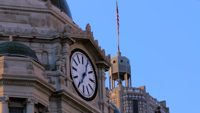Courthouse and skyscraper static shot.  Close-up of courthouse clock reads 7:05, and could pass for early morning or evening.  Clear blue sky.  Some pigeons fly around. - HD stock video clip
