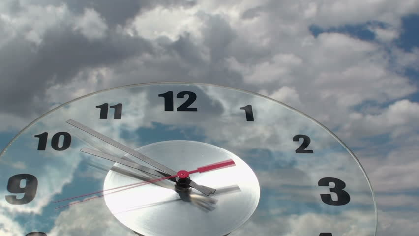 Time lapse, Clouds evaporate as they glide over transparent, ticking clock face.   - HD stock video clip