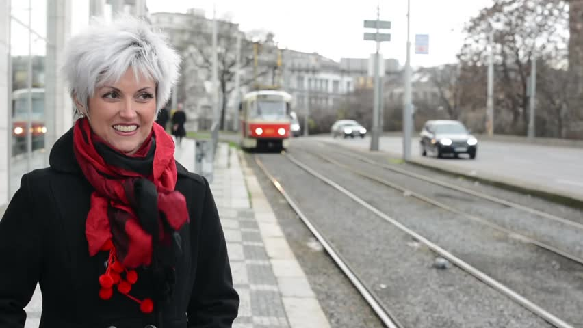 middle aged woman waits on tram in city (urban street) - winter