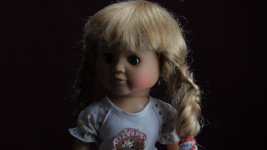 Doll terrible: he says, turns his head and blinks. In the shadows of the doll says turning his head and blinking. Scary doll for a holiday Halloween