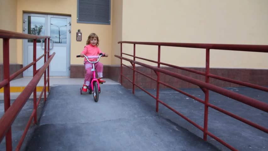 little girl with rucksack pedaling on bicycle near apartment block