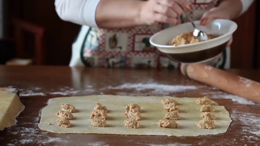Video clip of woman preparing agnolotti pasta: places the filling on the sheet and covers with another pasta sheet.
