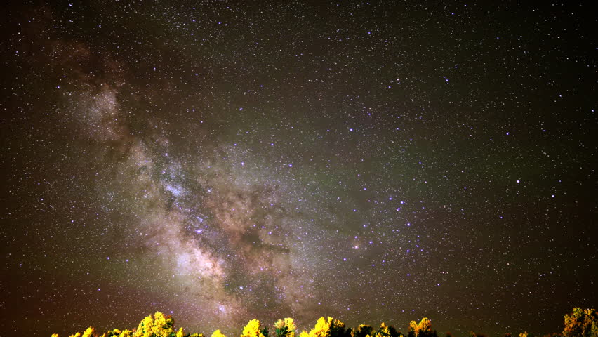 4K Astrophotography time lapse footage with tilt down motion of milky way galaxy over alpine forest in Utah