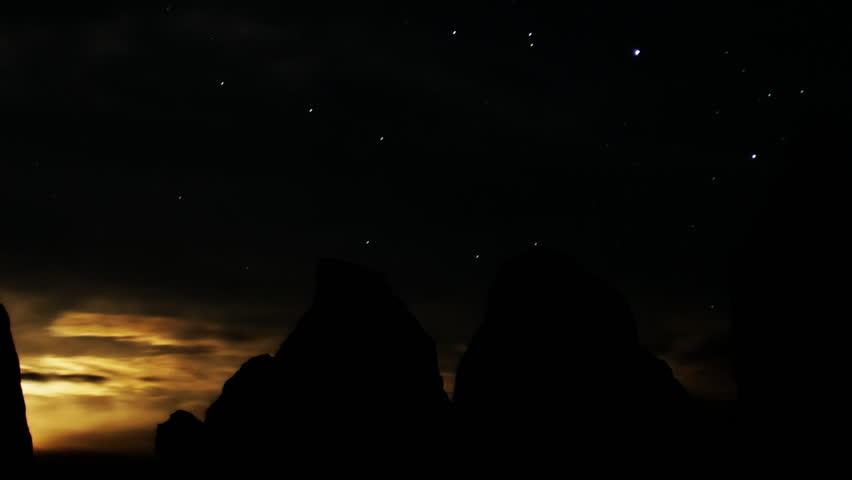 Astrophotography time lapse footage with zoom out motion of moon rising over monolithic formation in the desert of Trona, California