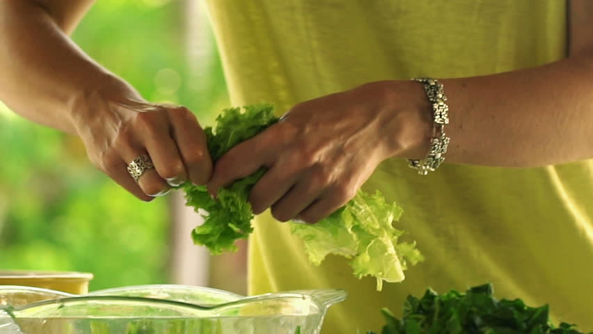Woman hands tearing salad leaves into glass bowl, slow motion shot at 120fps