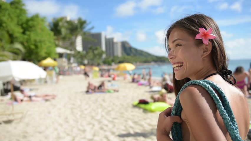 Woman going to the beach wearing beach bag smiling happy on vacation holidays travel on Waikiki Beach, Honolulu, Oahu, Hawaii, USA.