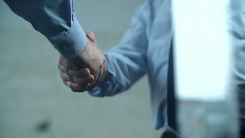 Slow motion of two cropped unrecognizable businessmen shaking hands