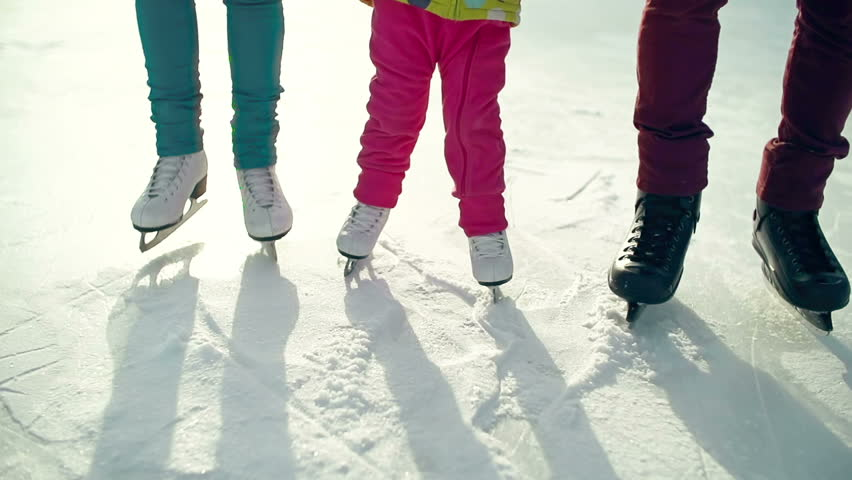 Tilt up of little child skating awkwardly supported by unrecognizable parents