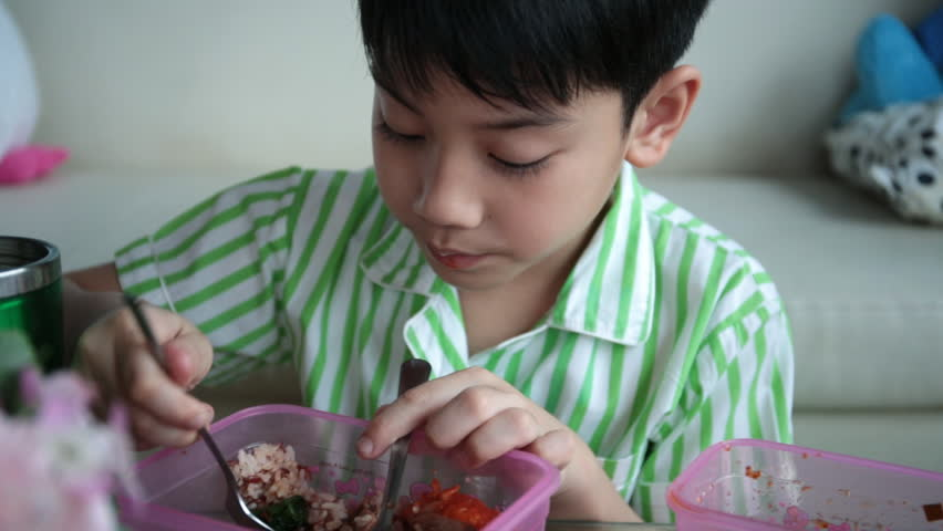 Little Asian Child Sitting At Table Eating Meal At Home