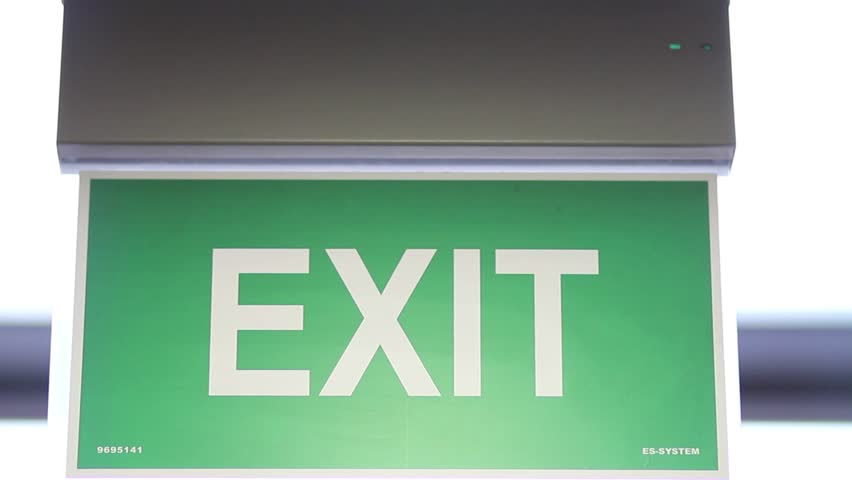 A front shot of an emergency exit sign which goes into focus and out of focus/In case of emergency follow this sign