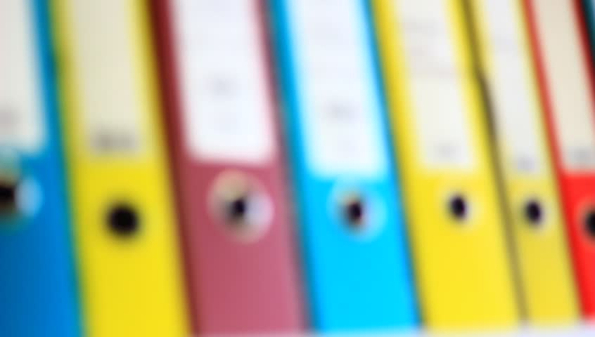 Colorful file folders in the office. Blurred clip, while camera pans. - HD stock footage clip