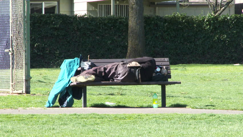 Camera zoom in on homeless person sleeping on city park bench during the day.