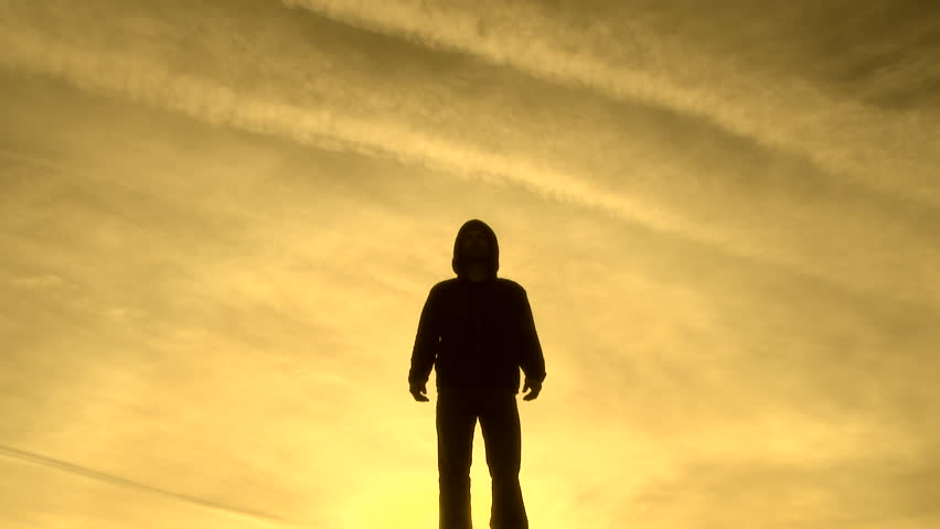 Model released, silhouette of hooded man standing amongst vivid and surreal, yellow sky.