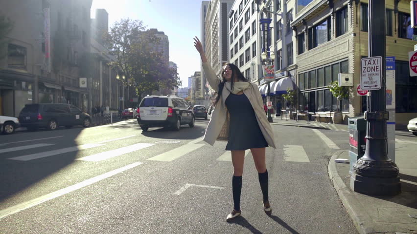 Mixed Race Young Woman Tries To Hail A Cab In The City On A Beautiful, Windy Day
