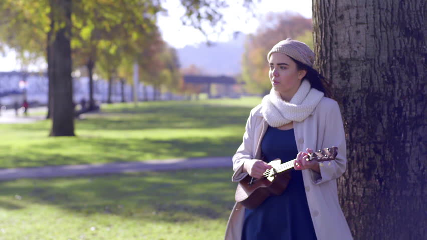 Mixed Race Young Woman Plays Her Ukulele, Under A Tree, In A City Park