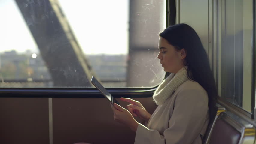 Mixed Race Young Woman Works On Her Tablet (On A Train Going Over A Bridge)