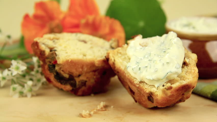 Fresh baked savory muffin cut in half then buttered with herb spread and sprinkled with parsley. - HD stock footage clip