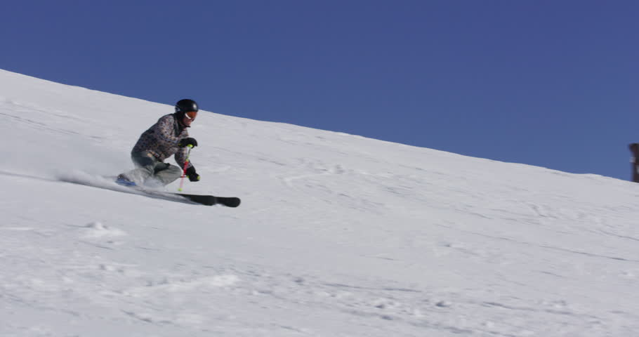 A skier carves while skiing down snowy slope leaves