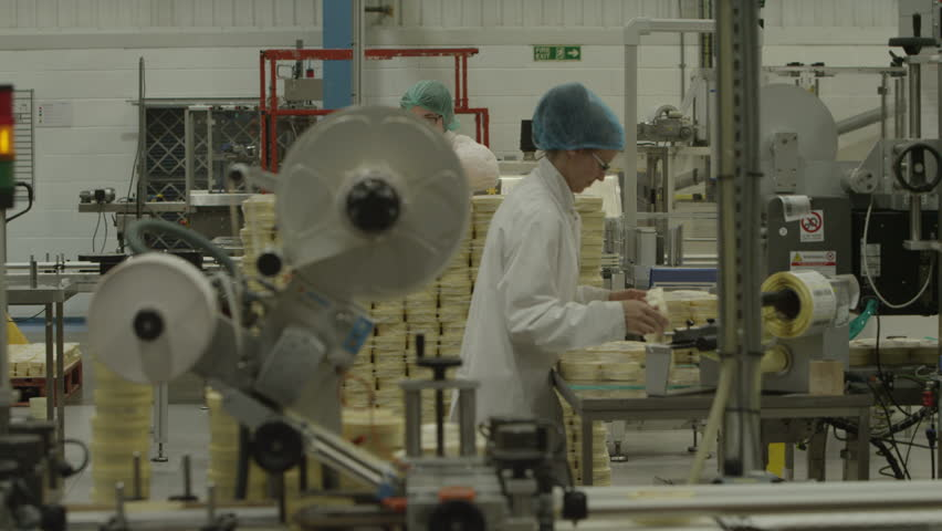 4K Worker applies labels to products. Pharmaceutical manufacturing facility