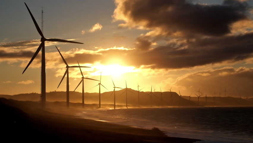 Wind turbine power generators silhouettes at stormy ocean coastline at sunset. Alternative renewable energy production in Philippines
