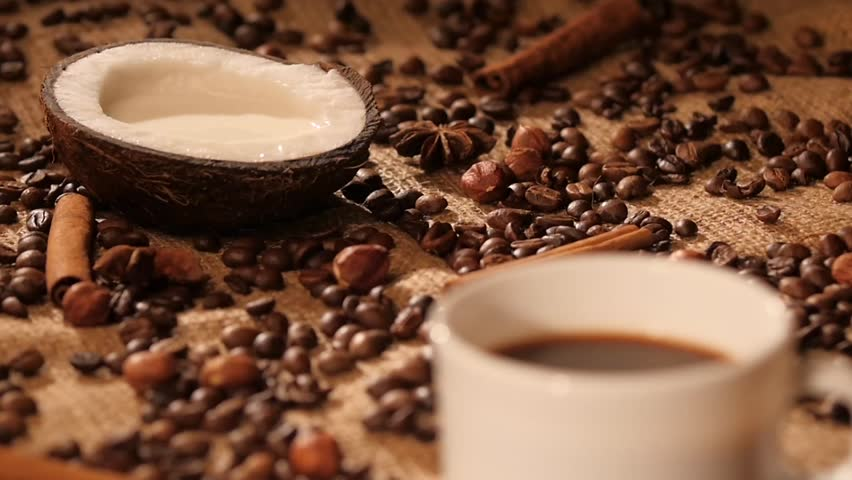 Pouring coconut milk into a cup of black coffee on background with coffee beans, cinnamon, anise, dynamic change of focus